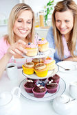 Positive young women eating cakes in the kitchen — Stock Photo