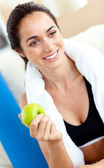 Smiling woman eating an apple on the sofa after working out in t — Stock fotografie