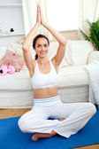 Smiling woman practicing yoga in her living-room — Stock Photo