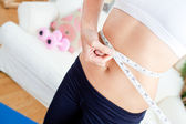 Close-up of a caucasian woman measuring her waist with a tape in — Stock Photo