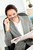 Bright businesswoman holding glasses and newspaper looking at th — Stock Photo