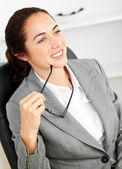 Assertive businesswoman holding her glasses sitting in her offic — Stock Photo