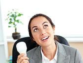 Empresaria sorprendida sosteniendo una bombilla en su ofi — Foto de Stock