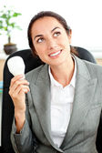 Considerado empresaria sostiene una bombilla en su mano sittin — Foto de Stock