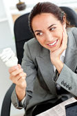 Thoughtful businesswoman holding a light bulb sitting in her off — Stock Photo