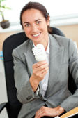 Attractive businesswoman holding a light bulb sitting in her off — Stock Photo