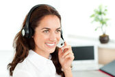 Smiling woman with headset working in a call center — Stock Photo