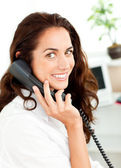 Lively young businesswoman talking on phone sitting at her desk — Stock Photo