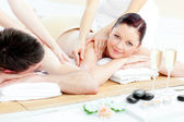 Charming young couple enjoying a back massage — Stock Photo
