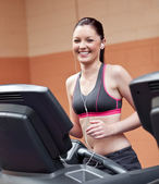 Radiant athletic woman with earphones exercising on a running ma — Stock Photo