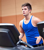 Concentrated athletic man training on a running machine — Stock Photo