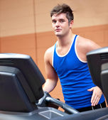 Good-looking man exercising on a running machine — Stock Photo