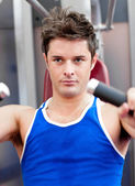 Confident young man using a bench press — Stock Photo