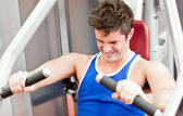 Strong athletic man using a bench press — Stock Photo