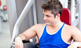 Relaxed young man using a bench press — Photo
