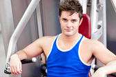 Self-assured young man using a bench press — Stock Photo