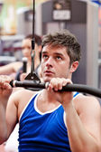 Muscular male athlete practicing body-building in a fitness center — Stock Photo