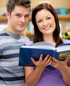 Bright couple of students reading a book — Stock Photo