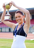 Ecstatic female athlete holding a trophee and a medal — Photo