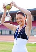 Extatische vrouwelijke atleet houdt een trophee en een medaille — Stockfoto