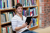Handsome male student reading a book sitting on the floor — Stock Photo