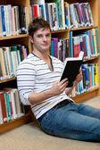 Knappe jonge man met een boek datum op de verdieping — Stockfoto