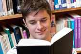 Portrait of a smiling male student reading a book sitting on the — Stock Photo