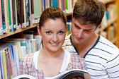 Young caucasian couple reading a book — Stock Photo