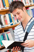 Cute male student reading a book — Stock Photo