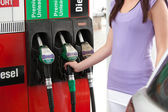Close-up of a young woman refueling her car — Stock Photo