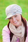 Happy young woman wearing cap and scarf smiling at the camera — Stock Photo