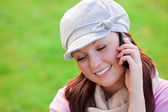 Smiling young woman wearing cap and scarf talking on phone on the grass — Stock Photo