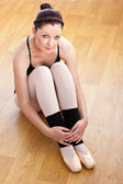Caucasian ballerina sitting on the floor — Stock Photo