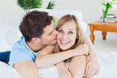 Handsome man kissing his joyful girlfriend both lying on the sof — Stock Photo