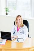 Loiro médico feminino sentado em seu escritório trabalhando em um laptop — Fotografia Stock