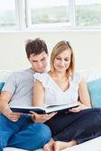 Coppia intelligente, leggendo un libro insieme seduti sul divano — Foto Stock