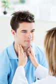 Close-up of a female doctor touching the throat of a patient in — Stock Photo
