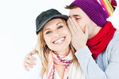 Young man with cap whispering something to his female friend — Stock Photo