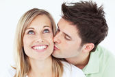 Careful man kissing his smiling girlfriend against a white backg — Stock Photo