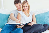 Beautiful loving couple reading a book on the sofa — Stock Photo