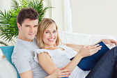 Young loving couple reading a book on the sofa — Stock Photo
