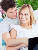 Portrait of a Happy young couple sitting on a sofa using laptop — Stock Photo