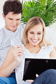 Young couple using laptop siting on a sofa — Stock Photo