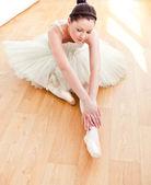 Piękna tancerka rozciąga się na podłodze — Zdjęcie stockowe