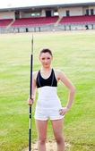 Confident athletic woman ready to throw a javelin standing in a — Stock Photo