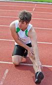 Bir st yarıştan önce yerdeki genç erkek sprinter streching — Stok fotoğraf
