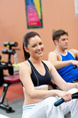 Hermosa mujer usando un remero con su novio en un gimnasio ce — Foto de Stock