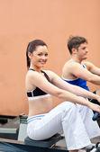 Atletische jonge met behulp van een roeier in een fitnesscentrum — Stockfoto