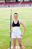 Joyful sporty woman holding a javelin standing in a stadium — Stock Photo