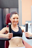 Beautiful athletic woman using a bench press smiling at the came — Stock Photo